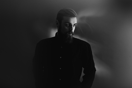 Black and white photo of a stylish man with a beard dressed in the black shirt stands in the fog