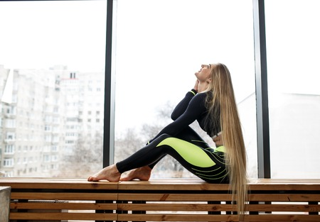 Beautiful athletic girl with very long blond hair is sitting on the wooden windowsill next to the panoramic windows in the gym