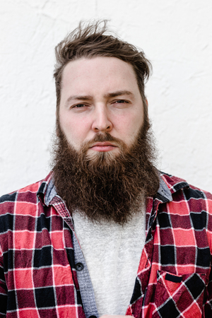 The portrait of the strong brutal man with a beard dressed in a checked shirt on the white background