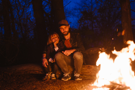 Happy father and his little son sitting together on the logs in front of a fire in a hike in the forest at the night.