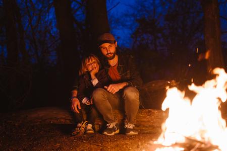 Heureux père et son petit fils assis ensemble sur les bûches devant un feu lors d'une randonnée dans la forêt la nuit.