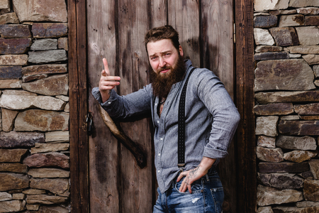 Strong brutal man with a beard and tattoos on his hands dressed in stylish casual clothes poses on the background of stone wall and wooden door Stockfoto