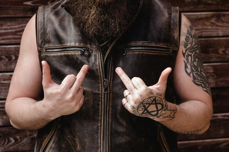 Strong brutal man with a beard and tattoos on his hands dressed in leather vest shows middle fingers 写真素材
