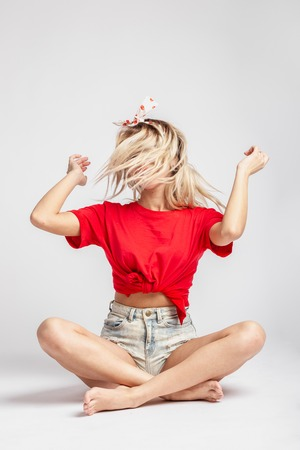 Young blond girl with a ribbon on her head dressed in short denim shorts and a red t-shirt poses sitting on the floor against a wall in the studio