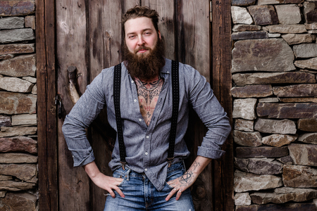 Strong brutal man with a beard and tattoos on his hands dressed in stylish casual clothes poses on the background of stone wall and wooden door