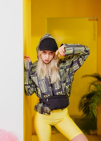 Young fashion girl blogger with black cap on the head dressed in a stylish black and yellow jacket and yellow shorts poses in the room with yellow walls  for the show room Reklamní fotografie