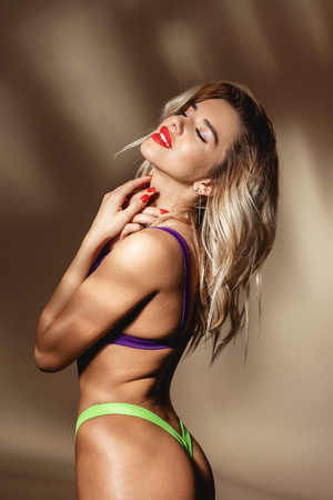 Sexy slim girl with red lipstick dressed in acid yellow and purple swimsuit is posing against a wall with shadows in the studio