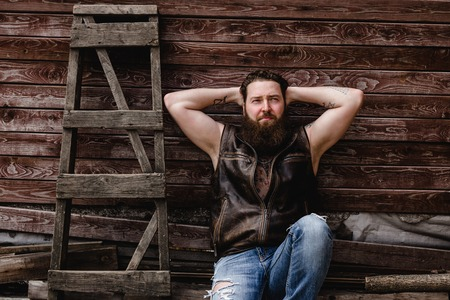 Strong brutal man with a beard and tattoos on his hands dressed in leather vest and jeans  sits on a wooden wall background next to a wooden ladder outside