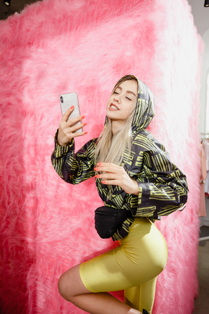 Fashion young girl blogger dressed in a stylish black and yellow jacket and yellow shorts takes a selfie on the smartphone possing on the background of pink fur wall