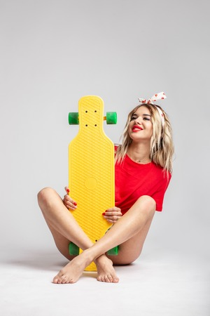 Blond girl in short denim shorts and a red t-shirt poses with a yellow skateboard sitting on the floor in the studio Reklamní fotografie