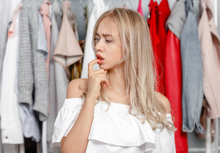 Young pretty girl blogger stands with a thoughtful expression on his face on the background of clothes hanging on a hanger in the wardrobe Reklamní fotografie
