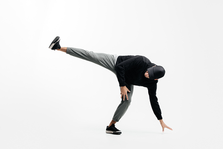Handsome young man wearing a black sweatshirt, gray pants and a cap is dancing breakdance Stock Photo