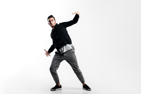 Stylish young dancer wearing a black sweatshirt and gray pants is dancing hip-poh on a white background