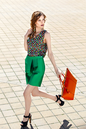 Beautiful women dressed in stylish green shorts and a bright top holding orange bag is walking in the city street on a summer day