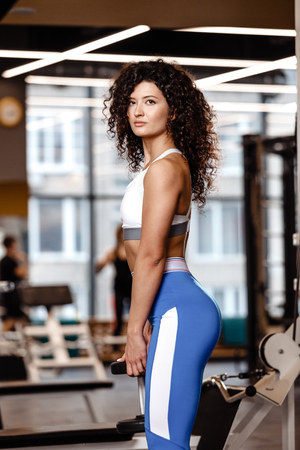 Slim girl with dark curly hair dressed in a sportswear is standing with the heavy dumbbell in her hands in the modern gym with big windows