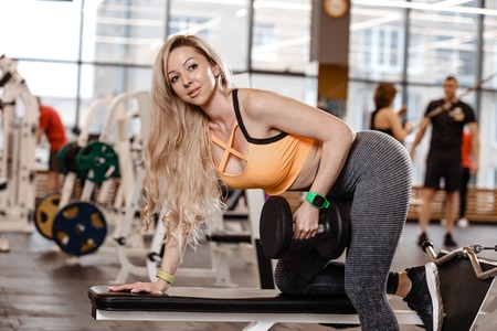 Athletic  blond girl with long hair dressed in a sportswear is doing exercise on the bench with dumbbells for triceps in the modern gym Banco de Imagens
