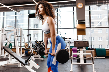 Good fit curly girl dressed in sports clothes is doing deadlift with barbell in the modern gym full of sun light