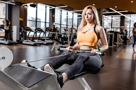The beautiful athletic girl with long blond hair dressed in a sportswear is doing sport exercises with equipment on the bench in the modern gym