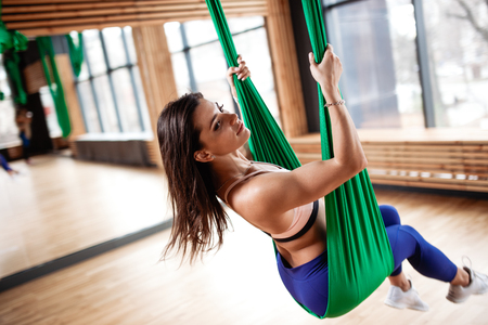 Beautiful young brunette girl  dressed in the sport clothes is doing fitness on the green aerial silk in the gym