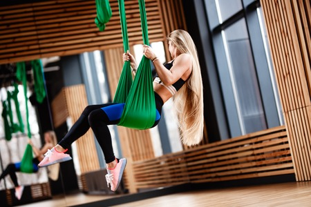 Athletic young girl with long blond hair dressed in the sport clothes is doing fitness on the green aerial silk in the gym