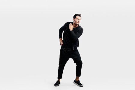 Handsome young  man dressed in a sport black clothes is dancing street dance.