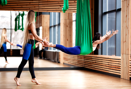 Two young athletic girls brunette and blonde are doing fitness on the green aerial silk in the modern gym Stock Photo