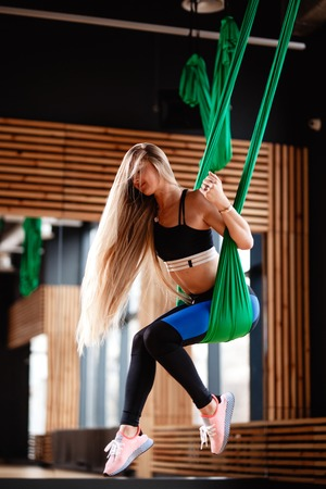 Young beautiful girl with long blond hair dressed in the sport clothes is doing fitness on the green aerial silk in the modern gym with big windows