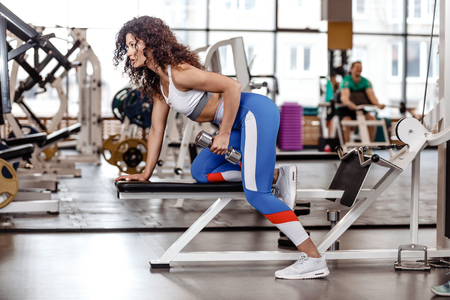 Athletic curly girl dressed in a sportswear is doing exercise on the bench with dumbbells for triceps in the modern gym Stock Photo - 124894344