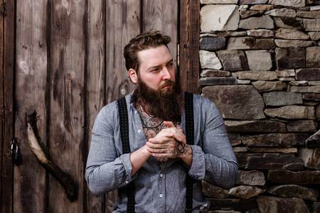 Brutal strong man with a beard and tattoos on his hands dressed in stylish casual clothes stands on the background of stone wall and wooden door Banco de Imagens