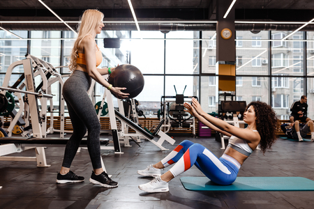 Two athletic girls dressed in a sportswear  are doing exercises for the press on the mat for fitness with fitness ball in the gym Stock Photo - 124894375