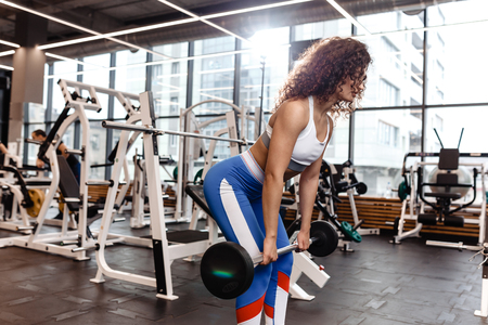 Good fit curly girl dressed in sports clothes is doing deadlift with barbell in the modern gym full of sun light Stock Photo - 124894377