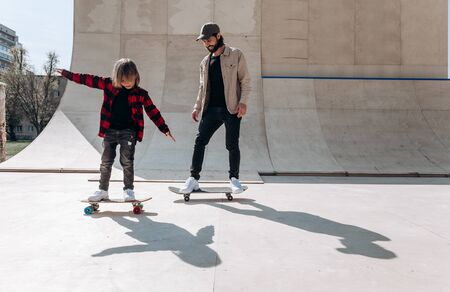 Young father and his son ride skateboards in a skate park with slides outside at the sunny day