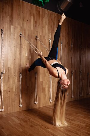 Beautiful slim girl  with very long blond hair dressed in a sportswear is doing stretching on special rope equipment in the modern gym with wooden decoration Banco de Imagens