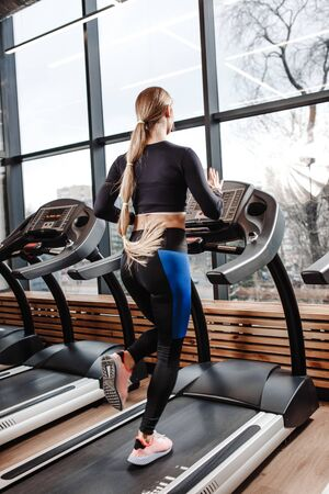 The athletic girl dressed in a sportswear is running on the treadmill in front of the windows in the modern gym Stock Photo - 124894425