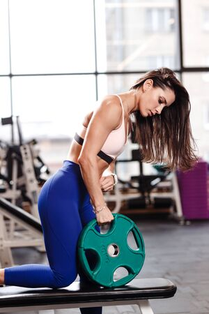 Young athletic brunette girl dressed in a sportswear is doing exercises with plate on the bench in the modern gym Stock Photo - 124894426