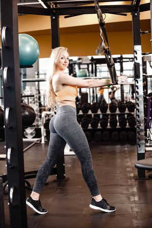 Slender blond girl with long hair has a TRX workout in the modern gym full of sun light