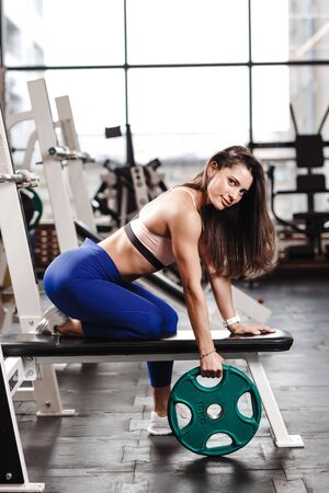 Young athletic brunette girl dressed in a sportswear is sitting on the bench with the plate  in the modern gym