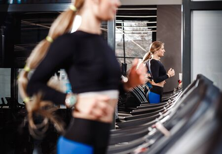 The athletic girl with long blond hair dressed in a sportswear is running on the treadmill in the modern gym
