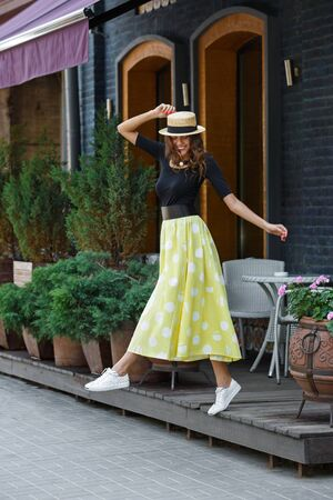 Stylish brunette girl dressed in black blouse and long yellow in white peas skirt walks in the city street on a sunny day