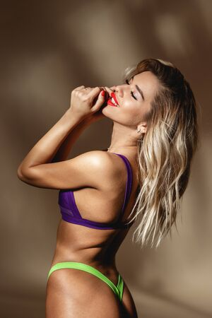 Shapely sexy girl with red lipstick dressed in acid yellow and purple swimsuit is posing against a wall with shadows in the studio