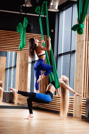 Two young athletic girls brunette and blonde are doing fitness on the green aerial silk in the modern gym Stock Photo - 124894527
