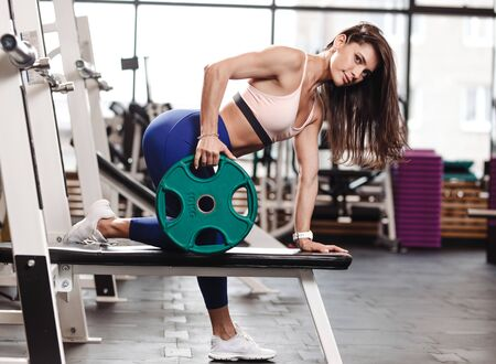 Young ahletic brunette girl dressed in a sportswear is doing exercises for back with plate on the bench in the modern gym