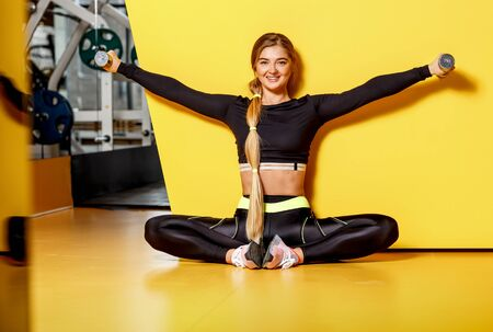 Beautiful athletic girl with long blond hair dressed in a stylish sportswear is sitting on the yellow floor next to the dumbbells by the yellow wall.