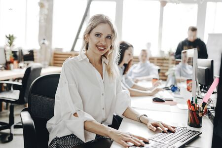 Young beautiful woman dressed in white shirt is working at the laptop sitting at the desk in a light modern open space office