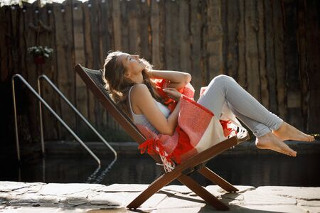 Young woman wrapped in a red and white plaid  sits in a folding chair next to the pool in the garden