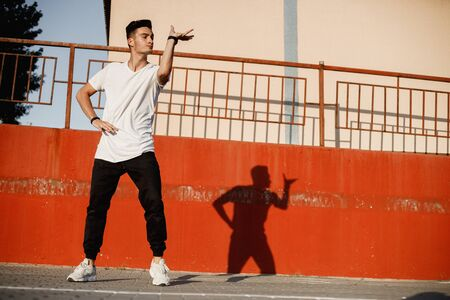 Stylish young guy dressed in jeans and white t-shirt is dancing brakedance in the street against a painted concrete wall in the sunny day