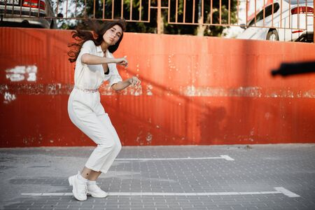 Young girl dressed in white shirt is dancing modern dance in the street against a painted concrete wall in the sunny day