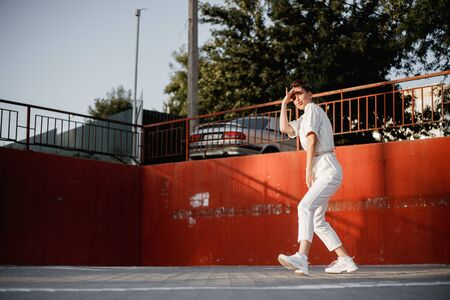 Young girl dressed in white shirt is dancing modern dance in the street on the background of parking in the sunny day