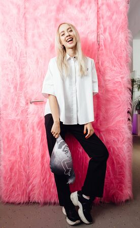 Young girl blogger dressed in stylish white shirt and black trousers poses with with a soft toy in the shape of a pigeon on the background of pink fur wall