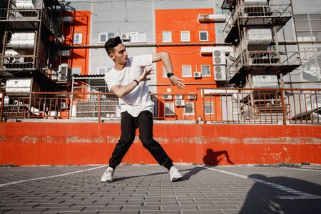 Young guy dressed in jeans and t-shirt is dancing modern dance in the street on the background of urban buildings in the warm day Banco de Imagens
